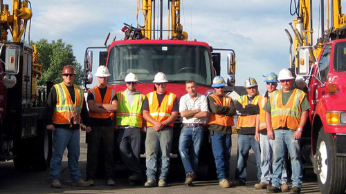 drilling engineers team standing in front of drilling rigs