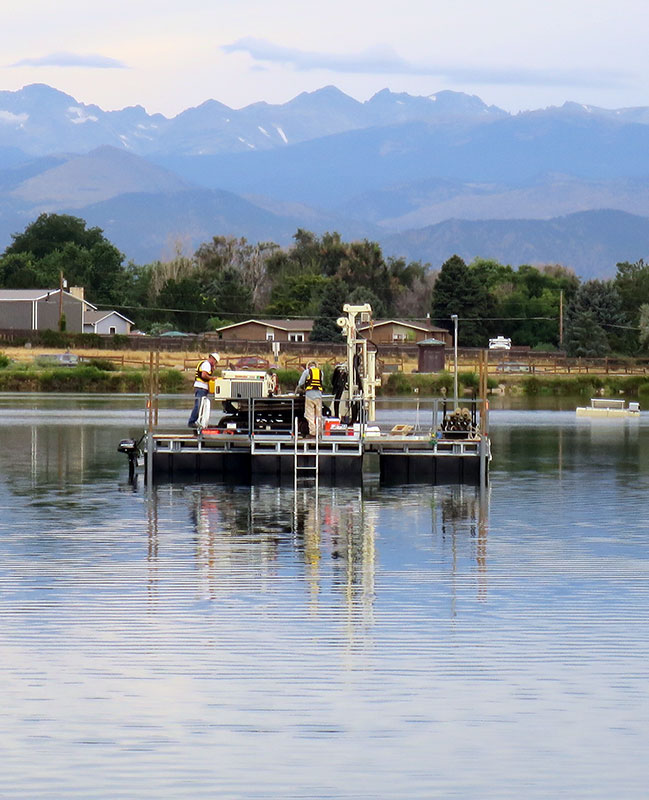 barge drilling on a lake with mountains in the background