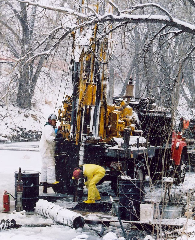 drillers drilling on a river bank in the snow